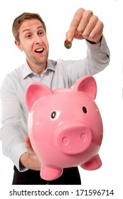 close-up pink piggy bank with a happy smiling businessman inserting a bank coin into it wearing a blue shirt on a white background.