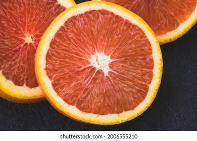 Closeup pink pulp of Cara Cara Orange sliced,on background,blurry light around