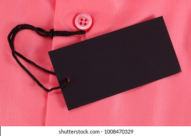 Close-up of pink shirt with round button and black label tag