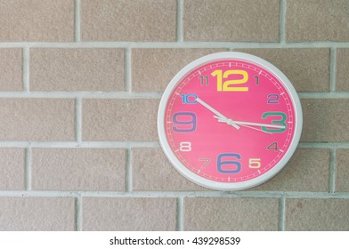 Closeup pink wall clock on brick wall textured background
