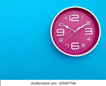 Closeup pink wall clock  set on blue background. The concept of