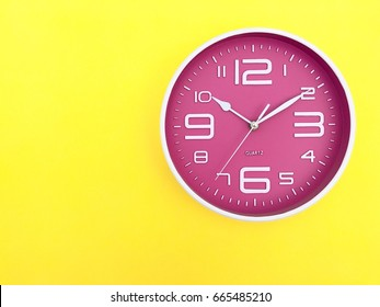 "Closeup A pink wall clock set on yellow background. The concept of ""The time is going on."" Top view with Selective focus. Copy Space."