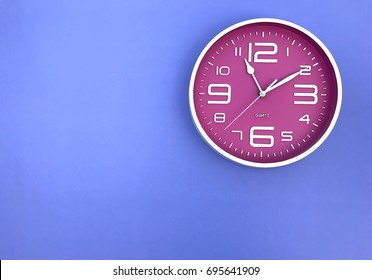 "Closeup A pink wall clock set on purple background. The concept of ""The time is going on."" Top view with Selective focus. Copy space."