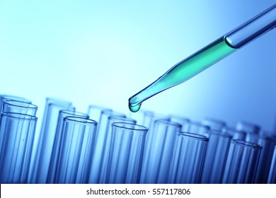 Closeup of a pipette dropping green sample into a test tube on light blue background