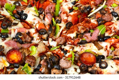 Closeup of a pizza with pepperoni, olive, sausage, onions, peppers, cheese, mushrooms and salami.
