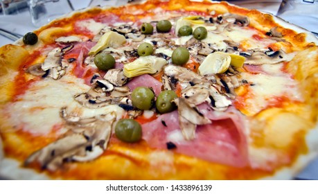 Close-up of Pizza Quattro Stagioni (Four Seasons). The artichokes represent spring, the olives summer, the mushrooms autumn and the ham winter.