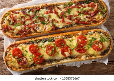 Close-up pizza sandwiches with bacon, mushrooms, tomatoes and cheese on a parchment on the table. horizontal view top from above