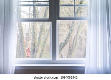 Closeup of plain white window curtains blinds in blue room interior indoors with wind decoration, outside bare tree in winter