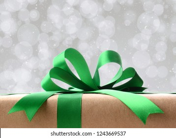 Closeup of a plain wrapped Christmas gift . Only the top portion of the present is shown against a silver bokeh background with snow effect.