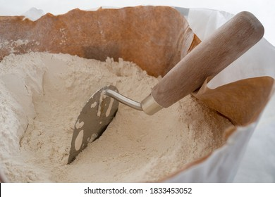 Close-up of plaster trowel in full open paper bag of putty powder for wall decoration,caulk or glaze.Concept of building materials.Finish coating in dry cement powder form.Selective focus,copy space - Shutterstock ID 1833453052