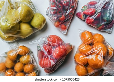 Closeup of plastic bags full of fruits and vegetables. Climate change and less plastic concept. Flat lay