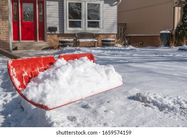 Closeup of a Plastic Red Shovel Full of Snow on a Sunny Day