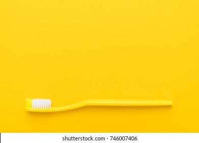 close-up plastic toothbrush on the yellow background with copy space
