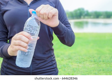 Close-up plastic water bottle in woman hand After Exercise
