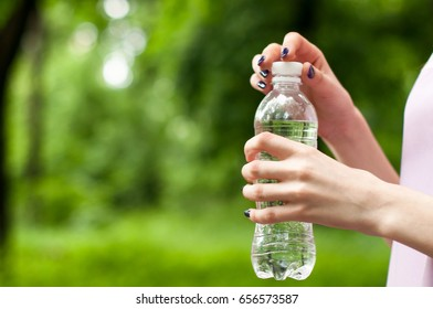 Close-up plastic water bottle in woman hand