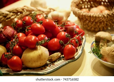 Closeup of a plate of fresh red tomatoes, potatoes, mushrooms and red onions.