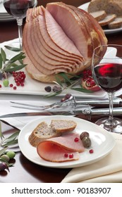 Closeup of plate with ham , bread and olives on dinning table set with glazed whole baked sliced ham, garnished with pomegranate.