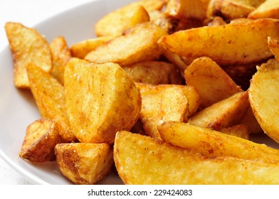 closeup of a plate with home fries on a white background