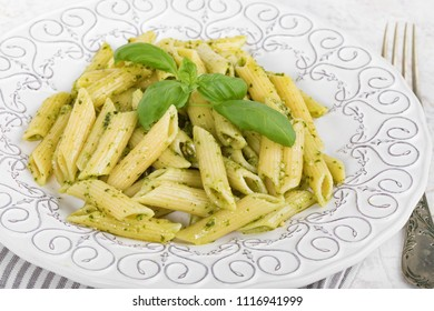Closeup of plate with penne rigate pasta with basil pesto.