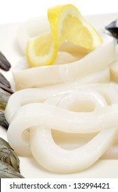 closeup of a plate with some raw squid rings on a white background