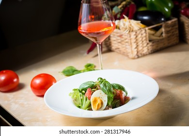 Closeup of plate of spring mix salad with strawberry, eggs and tuna