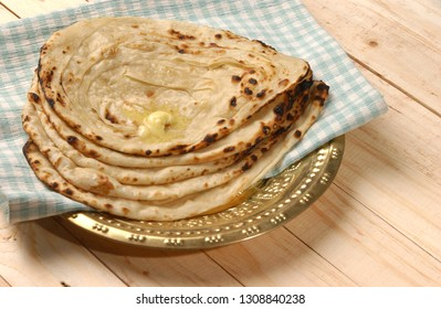 Close-up of plate with warm butter tandoori roti or Punjabi Roti or flatbread with ghee on brass plate  wooden table in the background.