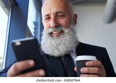 Close-up of pleased gentleman age of 50-60 holding cup of coffee and surfing in phone