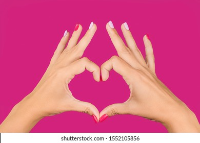 Closeup point of view photography of hands of beautiful young woman making heart gesture isolated on bright pink background. Love and happiness concept. Nails with trendy 2 colours manicure.