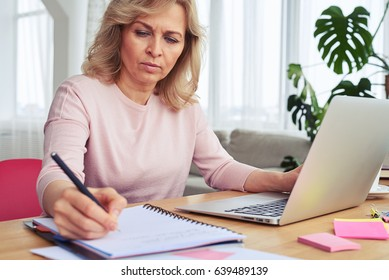 Close-up of pokerfaced woman writing while working in laptop