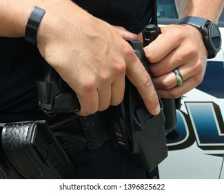 A close-up of a police officer holding the taser on his utility belt.