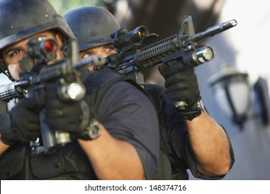 Closeup of police officers aiming with guns