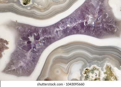 Closeup of a polished banded Agate geode filled with purple Amethyst Quartz crystals.