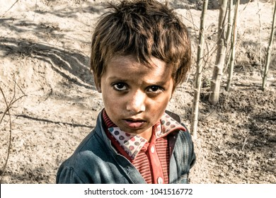 closeup of a poor staring hungry orphan boy in a refugee camp with sad expression on his face and his face and clothes are dirty and his ayes are full of pain