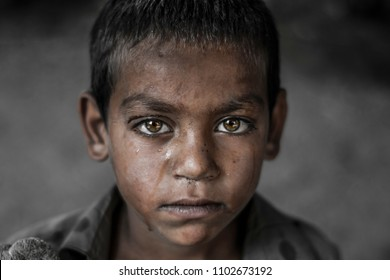 closeup of a poor staring hungry orphan boy in a refugee camp with a sad expression on his face and his face and clothes are dirty and his eyes are full of pain