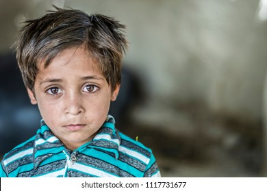 closeup of a poor staring hungry orphan boy in a refugee camp with sad expression on his face and his face and clothes are dirty and his eyes are full of pain