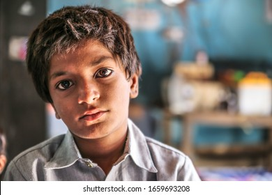closeup of a poor staring hungry orphan boy in a refugee camp with sad expression on his face and his eyes are full of pain