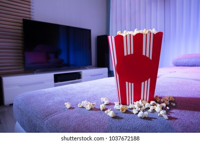 Close-up Of Popcorn On Couch In Living Room At Night