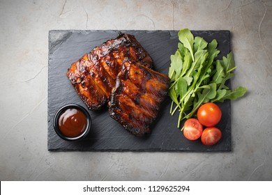 Closeup of pork ribs grilled with BBQ sauce and arugula. Tasty snack to beer on a stone Board for filing on old concrete background. Top view