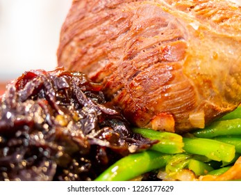 Closeup of a pork roast with green beans and glazed onion