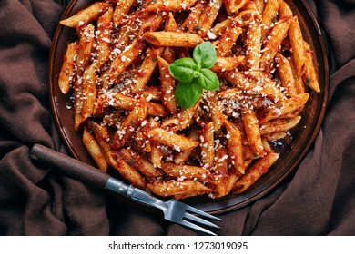 close-up of a portion of classic italian penne arrabiata in a bowl with basil and freshly grated peccorino cheese on an old wooden table, view from above, flatlay