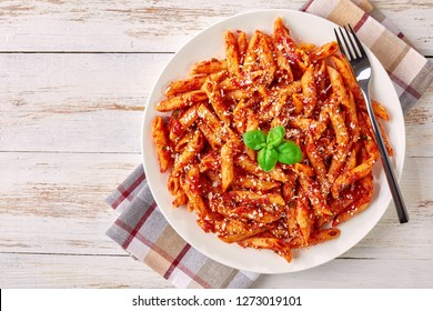 close-up of a portion of classic italian penne arrabiata on a plate with basil and freshly grated peccorino cheese on a white rustic wooden table, view from above,
