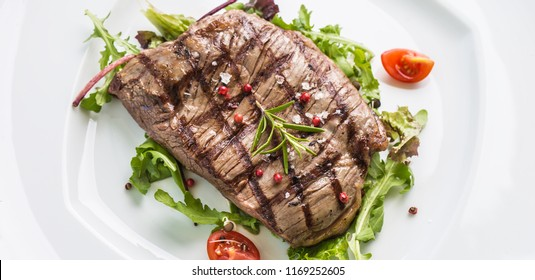 Close-up portion of juicy flank steak from vegetable salad salt pepper and rosemary on white plate.