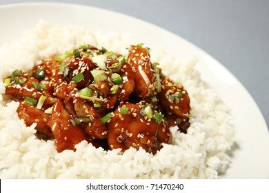A close-up of a portion of sesame chicken with rice served on a white plate