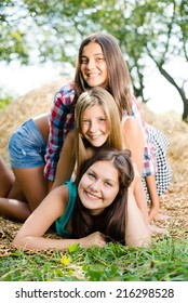 closeup portrait of 3 pretty girls having fun relaxing lying on hay happy smiling with excellent white teeth & looking at camera on green summer outdoors copy space background