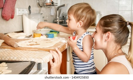 Closeup portrait of 3 years old toddler boy making cookies with mother. CHild holding baking pan and putting cookies on it