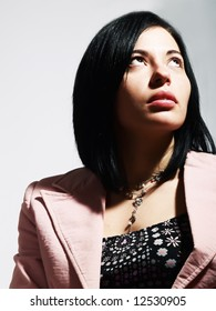 A closeup portrait about an elegant trendy woman with black hair who is looking up and she is dreaming something. She is wearing a nice dress, a stylish necklace and a pink coat.