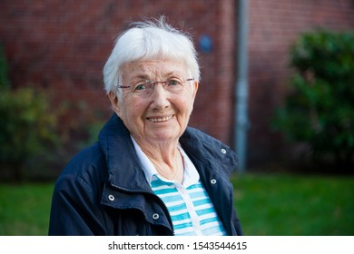 Closeup portrait of active smiling senior lady, over 90 years old, walking on the street