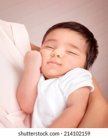 Closeup portrait of adorable Arabic child sleeping on mothers hands, little innocent baby, peace and harmony concept