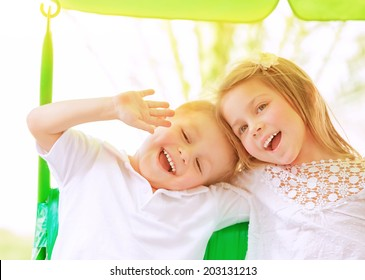 Closeup portrait adorable children having fun on swing outdoors, best friends playing on backyard in daycare, healthy and happy lifestyle, strong friendship concept