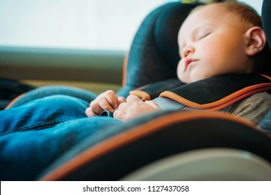 close-up portrait of adorable little baby sleeping in child safety seat in car